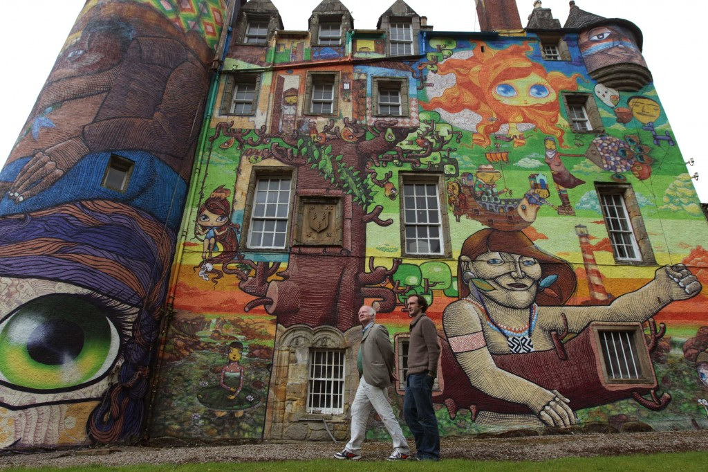 The Earl of Glasgow, Patrick Boyle, and his son David, pose for photographers next to graffiti paintings by Brazilian artists on the walls of Kelburn Castle near Largs, Scotland